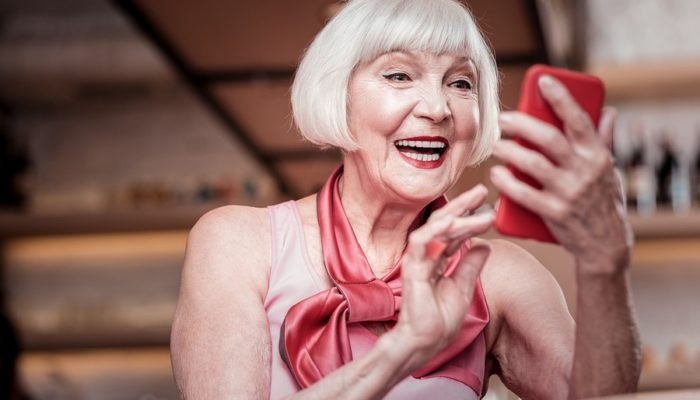Beautiful stylish old lady with short haircut checking social media