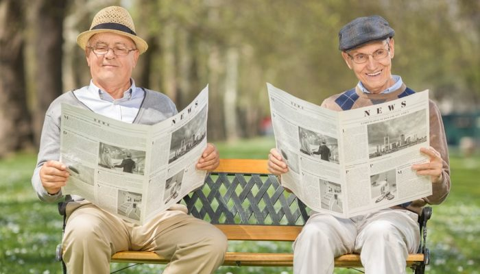 Two senior gentlemen sitting on a bench in park and relaxing by reading newspapers